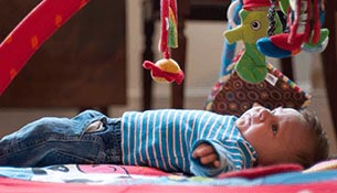A three month old infant lying on a bed staring at toys in the air