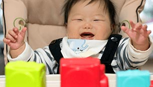 A six month old Asian infant opening its mouth and opening its arm
