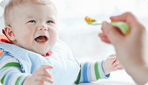 An eight month old infant staring at a spoonful of food in the air