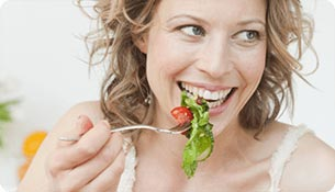 A smiling woman about to eat vegetables from her fork