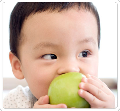 Baby with apple in mouth.