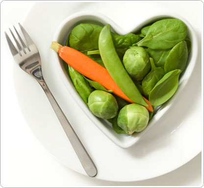 The top of a heart shaped, white bowl containing spinach, peppers, sugar snap pees and asparagus.