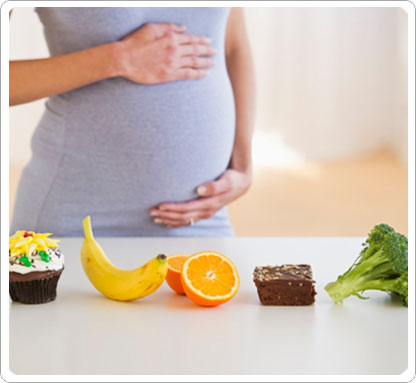 Pregnant woman with her hand on her stomach behind a cupcake, banana, orange, brownie and broccoli.