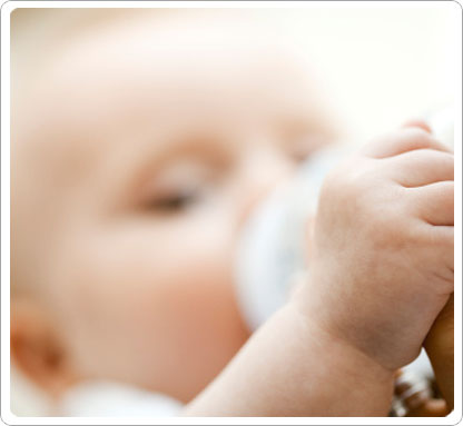 Closeup of baby holding bottle, feeding.