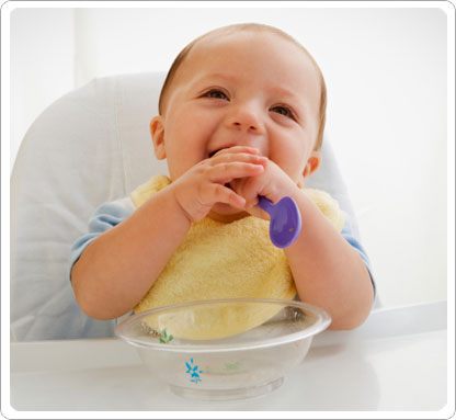 Baby laughing with spoon in mouth.