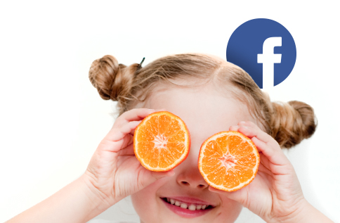 Little girl poses with two slices of oranges as eyes