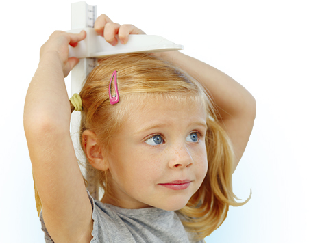 PediaSure® image of a young girl measuring her height