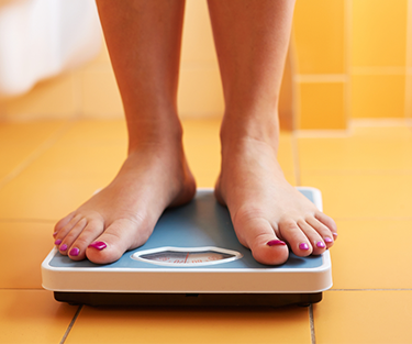 A lady standing on a weight scale