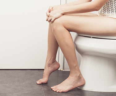 A lady sitting on the toilet constipated