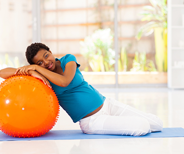 Pregnant woman leaning on exercise ball