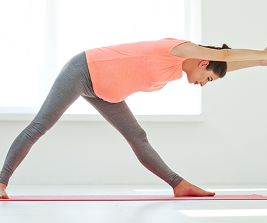 A lady bending forward in a yoga session