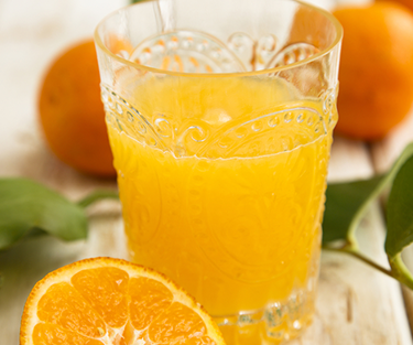 A glass of orange juice with oranges on the side