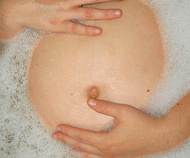 A pregnant lady laying in the bath touching her stomach]