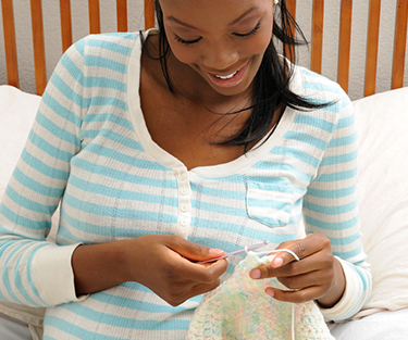 A pregnant lady knitting