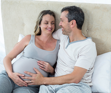 A pregnant couple sitting on a bed touching the stomach
