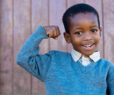 A boy smiling flexing his arm