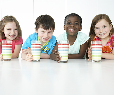 Children sitting together drinking a PediaSure shake