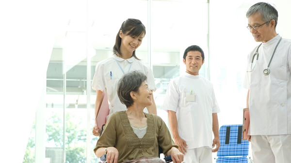 Image of female patient in wheelchair surrounded by her medical team