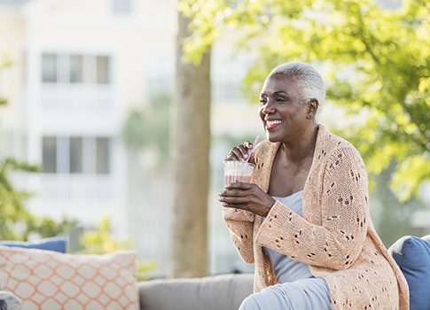 senior woman relaxing on a patio, drinking an oral nutrition supplement.