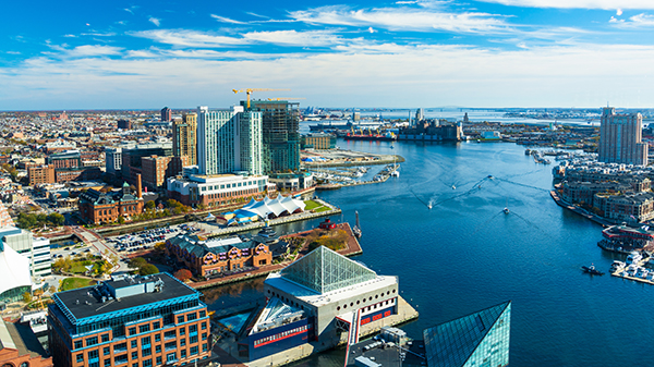 An aerial view of the Patapsco River and waterfront on a sunny day in Baltimore, MD.