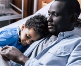 Father reads to young son, a hospitalized patient, while lying together on a hospital bed.