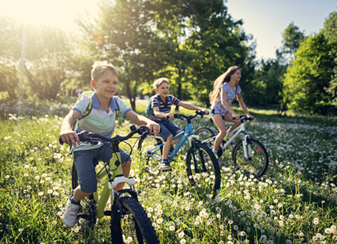Two boys and a girl ride bikes through a field on a pretty day