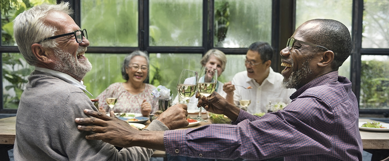 A group of older friends laugh while sitting around a table