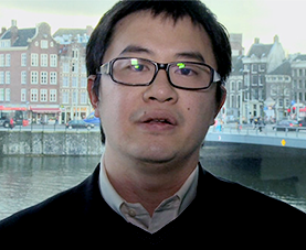 A headshot of Julian Lui delivering opening remarks to his presentation with a cityscape in the background.