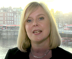 A headshot of Kate Ward delivering opening remarks with a cityscape in the background.
