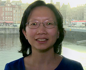 A headshot of Marian Aw delivering opening remarks with a cityscape in the background.