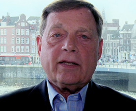 A headshot of Robert E. Black delivering opening remarks with a cityscape in the background.