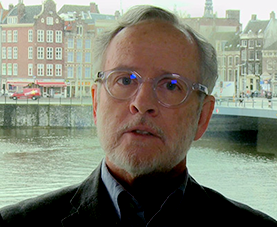 A headshot of Robert Murray delivering opening remarks with a cityscape in the background.