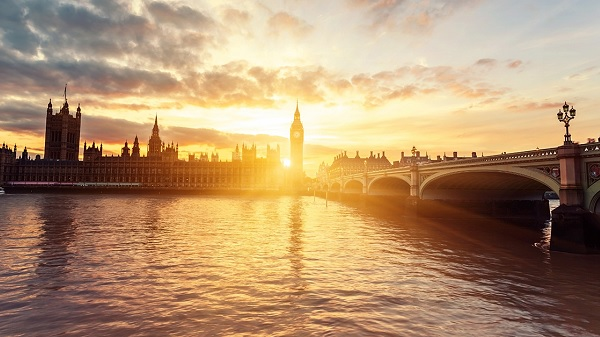 A shoreline view of London Bridge and Parliament as the sun is setting