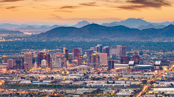 A sunset view of downtown Phoenix, Arizona, with a distant view of the Phoenix Mountain Reserve in the backdrop