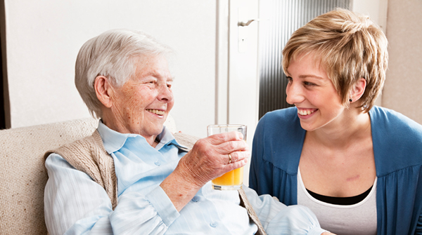 An elderly lady enjoying a glass of orange juice with a younger lady.