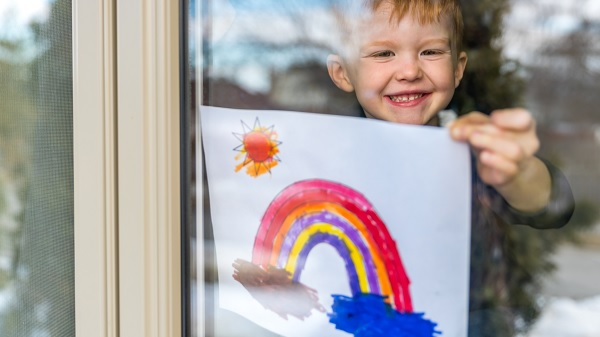 Child holds rainbow painting against window