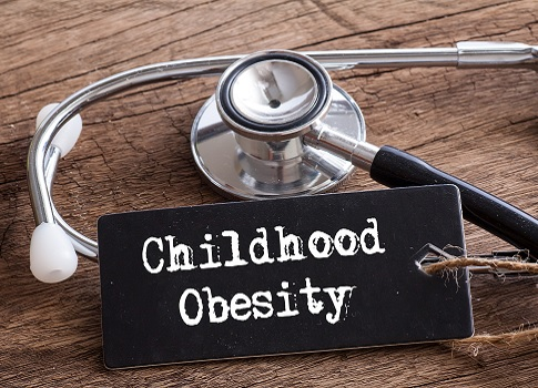 "Stethoscope and placard that reads ""Childhood Obesity"" both sit on a wooden table"