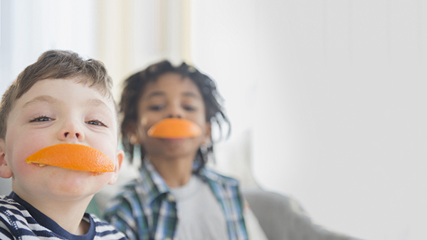 Two children with orange segments in their mouths.