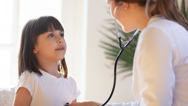 A doctor listens to a little girl's lungs