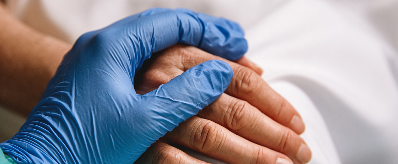 A hand in a medical glove holding a patient's hand.