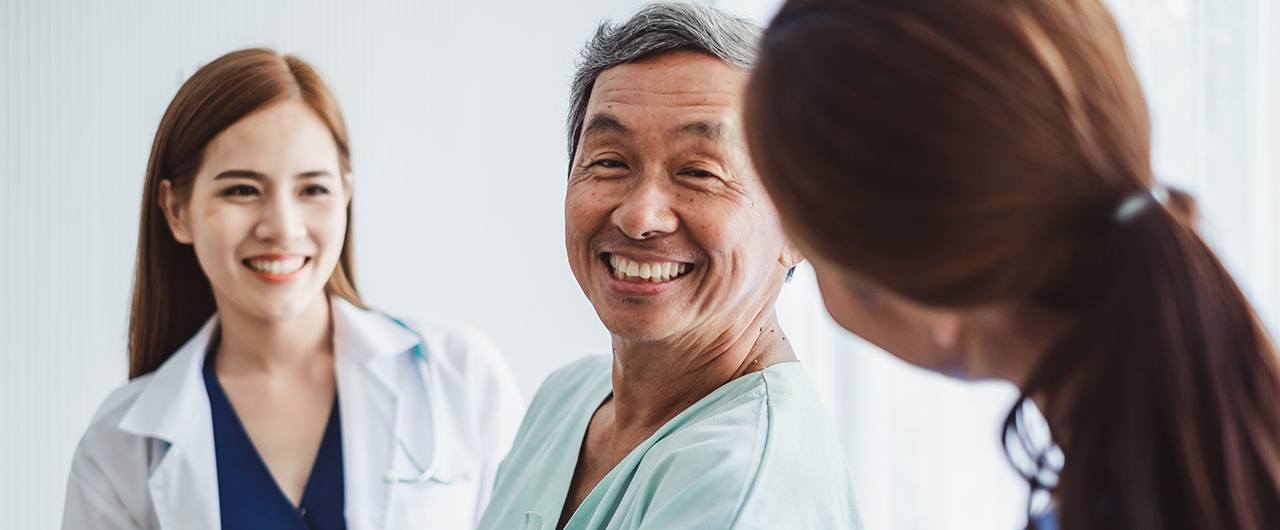 Male patient smiles at two female healthcare professionals