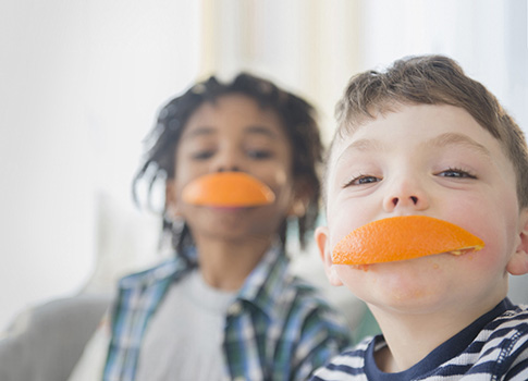 Two little boys smiling with orange peels in their mouths.