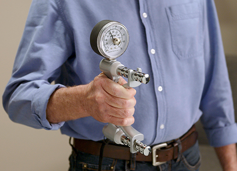 Medical professional holding a grip strength tool.