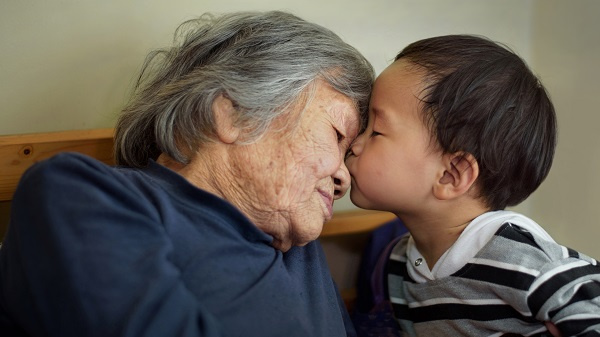 A little boy kisses his grandmother on the forehead