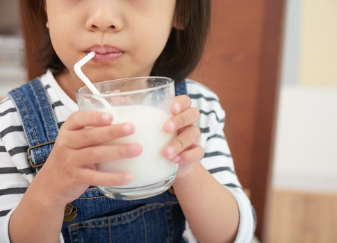 Little girl drinking a glass of milk through a straw