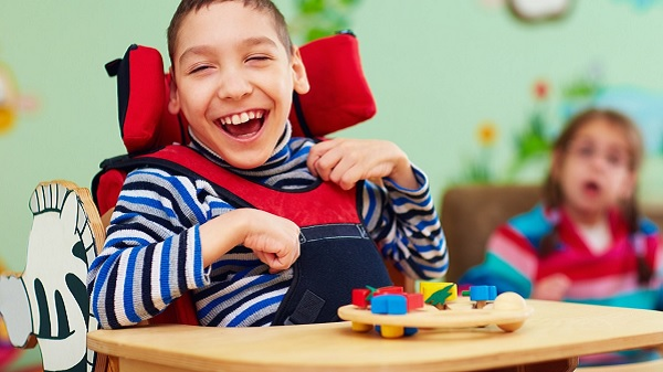 Child in wheelchair laughs at something offscreen
