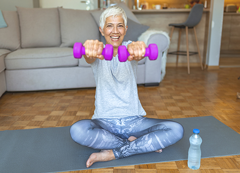 A middle-aged woamn on a yoga mat holding some weights