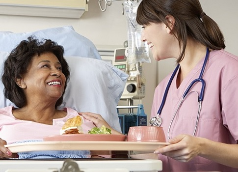 Nurse smiles while bringing food tray to hospitalized patient