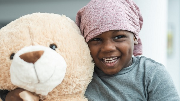 Little girl with cloth covering on head hugs an oversized teddy bear
