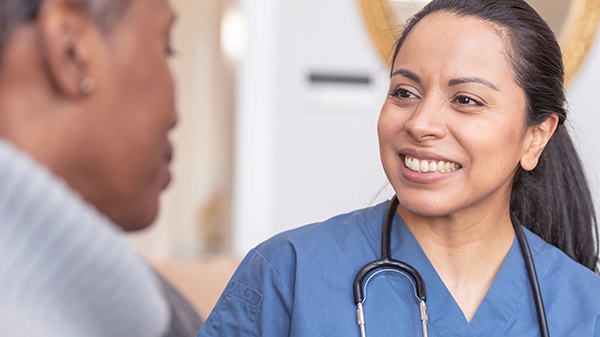 Female physician smiles at female patient